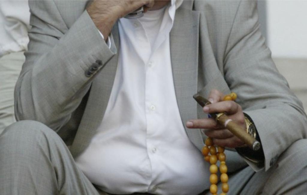 Ο Ηλίας Καραβόλιας στηλιτεύει τηνελληνική αντίληψη του χρόνου πριν την κρίση: το κομπολόι στο ένα χέρι και το Rolex στο άλλο.Σήμερα, ο χρόνος μετράει καταλυτικά. Το ρολόι στο χέρι (μαιμού αυτή την φορά) γίνεται μετρητής εργασίας και πηγή άγχους. new deal